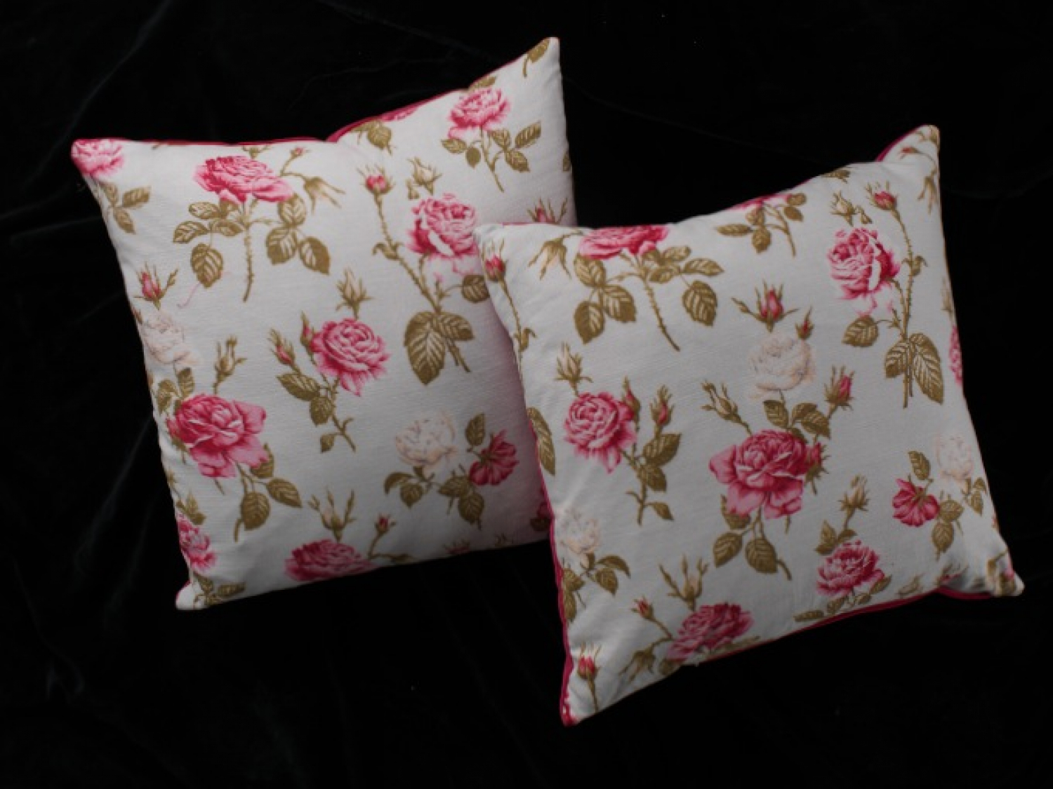 A pair of pink and white floral vintage cushions